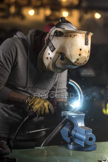 Portrait of mechanic welding pipe at workshop — Stock Photo