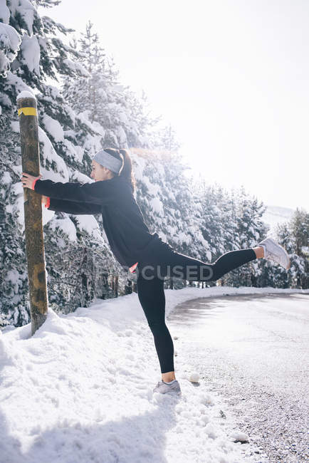 Side view of leaning on post and warming up muscles on snowy countryside road — Stock Photo