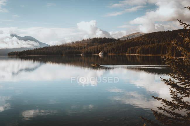 Vista a distanza del motoscafo galleggiante sul lago in collina — Foto stock