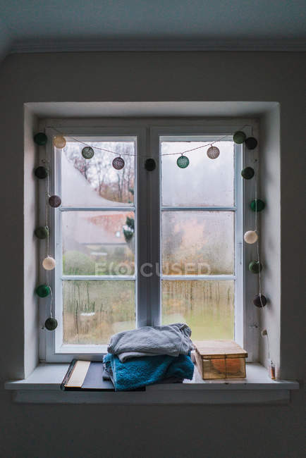 Fenster mit Kondensation und Stapel Handtücher auf Fensterbrett dekoriert. — Stockfoto