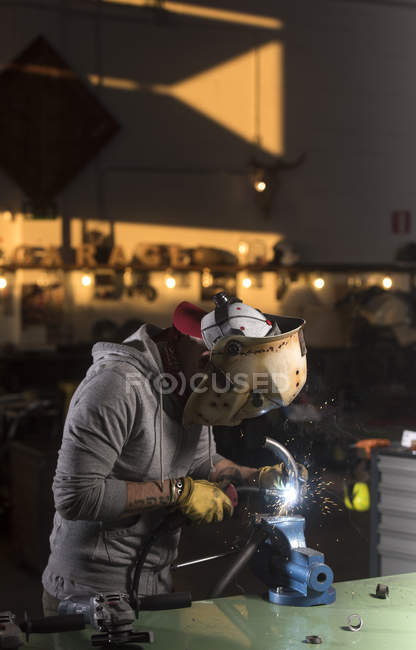 Side view of mechanic in mask welding pipe at workshop — Stock Photo