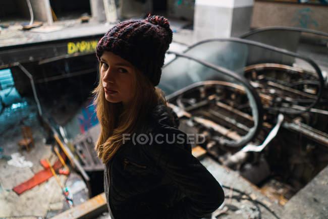 Mujer joven en sombrero posando en edificio envejecido y mirando a la cámara - foto de stock