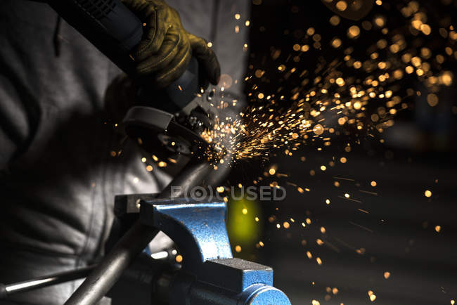 Crop mechanic hands using angle grinder on pipe at workshop — Stock Photo