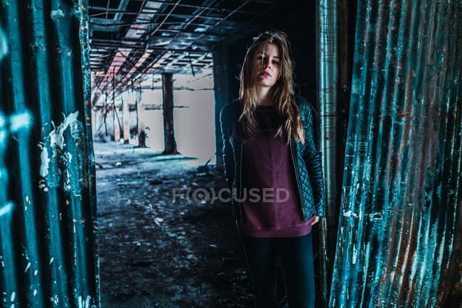 Bastante joven atractiva mujer de pie y posando en el viejo edificio gruñón . - foto de stock