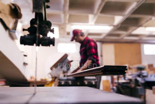 Verwischter Tischler trägt Holz in Werkstatt — Stockfoto