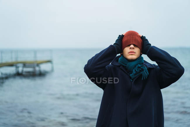 Portrait of man standing at seaside and putting hat on eyes — Stock Photo