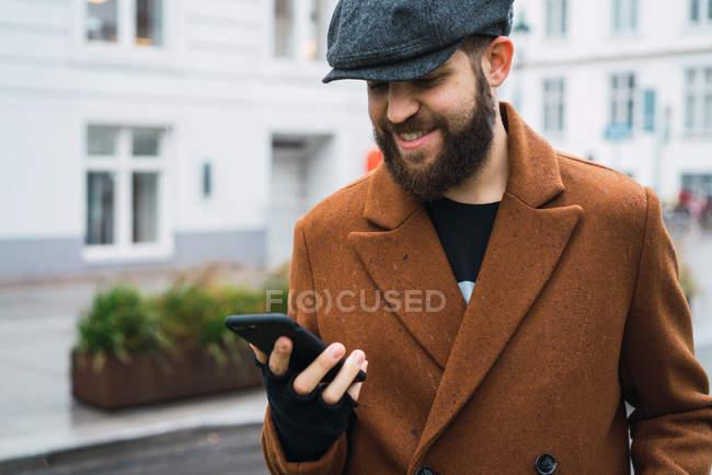 Усміхаючись бородатого мужчини в Кап за допомогою смартфона на вулиці — стокове фото