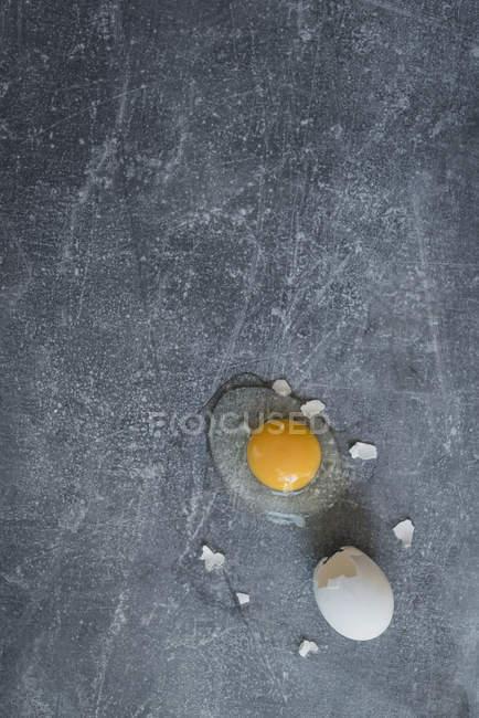 Сверху вид сломанной сырое яйцо на серой поверхности. — стоковое фото