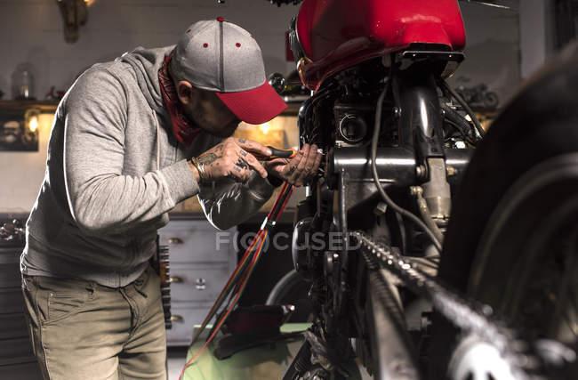Вид збоку механік ремонту Користувальницькі мотоцикл на семінарі — стокове фото