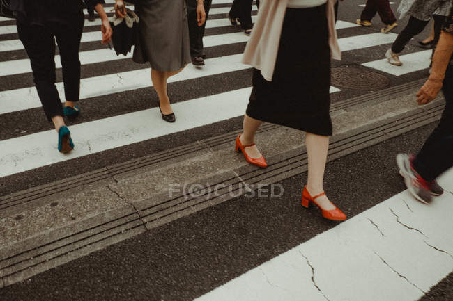 Crop pedestrians walking on crosswalk in city street — Stock Photo