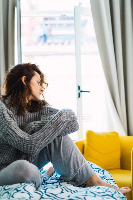 Vista lateral de la joven sentada en la cama en casa y mirando hacia otro lado . - foto de stock