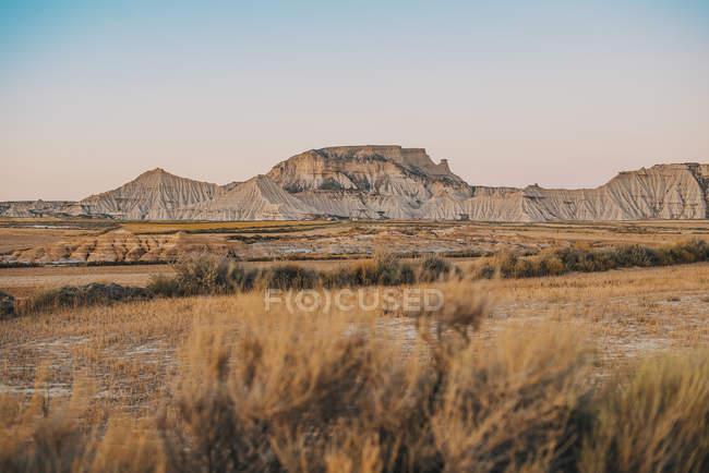 Paisagem de colinas grandes areias e campo seco num dia sem nuvens. — Fotografia de Stock