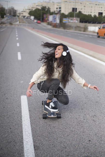 Cheerful girl in headphones riding longboard on street scene — Stock Photo
