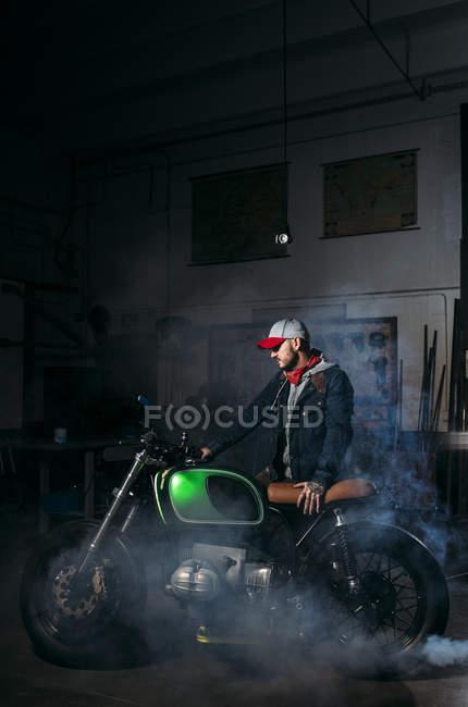 Side view of mechanic actuating custom motorbike at workshop — Stock Photo