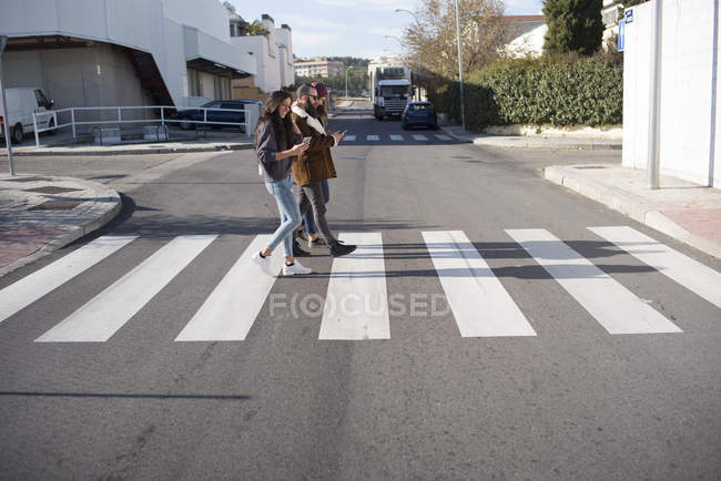 Side view of group of friends walking at zebra crossing — Stock Photo