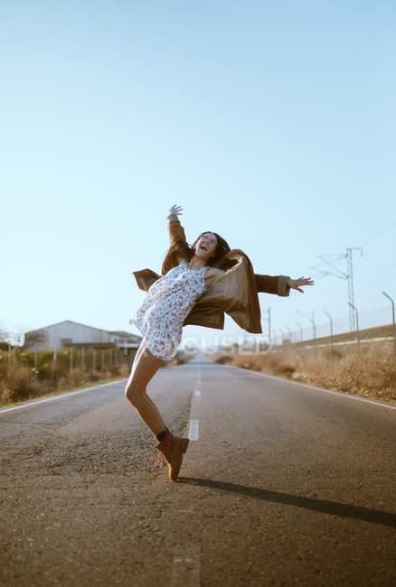 Fröhliche junge Frau posiert und Spaß auf Asphaltstraße in Landschaft — Stockfoto