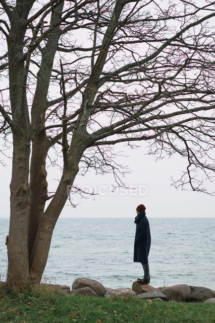 Side view of man in warm clothes posing on stone at seaside in cold day. — Stock Photo