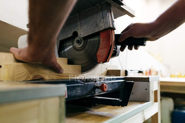 Crop carpenter hand cutting piece of wood with mechanic saw — Stock Photo