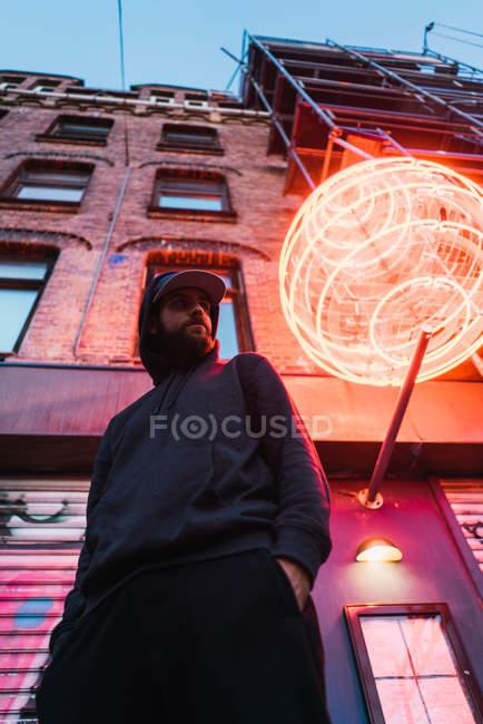 Bottom view of man posing under neon circle at street — Stock Photo