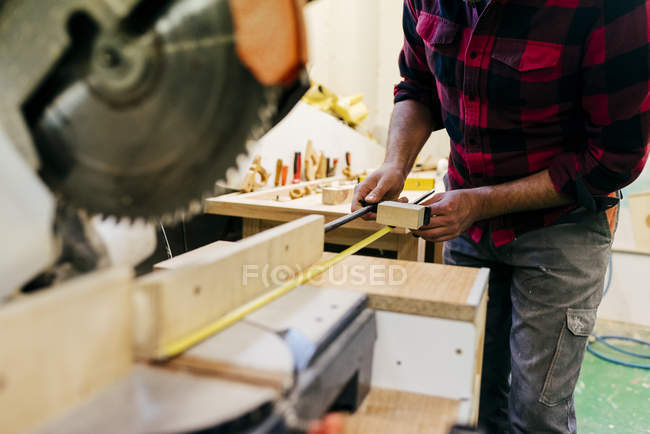 Geschnittener Tischler nimmt Maß in Stück Holz — Stockfoto
