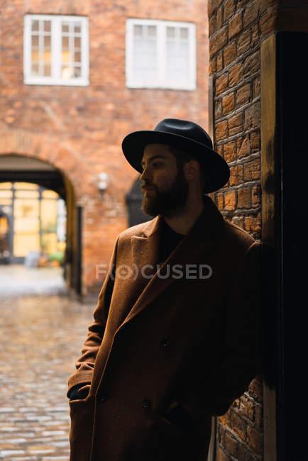 Бородатого мужчини в пальто, спираючись на стіні в arch — стокове фото
