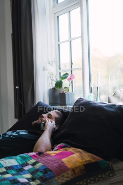 Vista lateral del hombre acostado en casa y hablando por teléfono - foto de stock