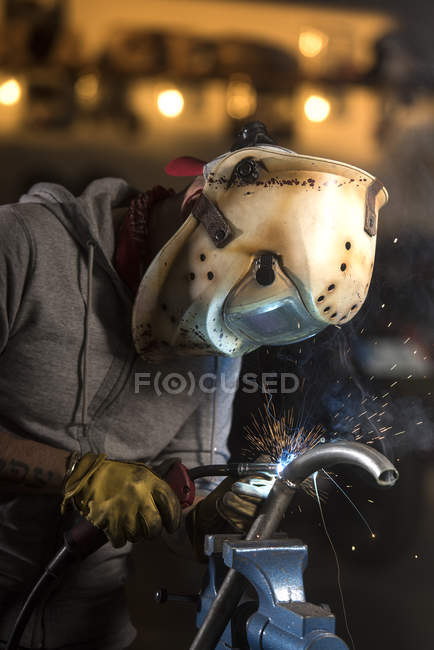 Portrait of worker welding pipe at workshop — Stock Photo