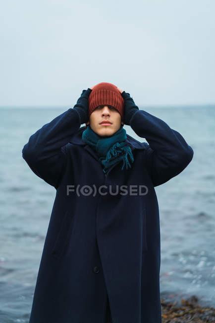 Porträt eines Mannes mit Hut auf Augen am Meeresufer — Stockfoto