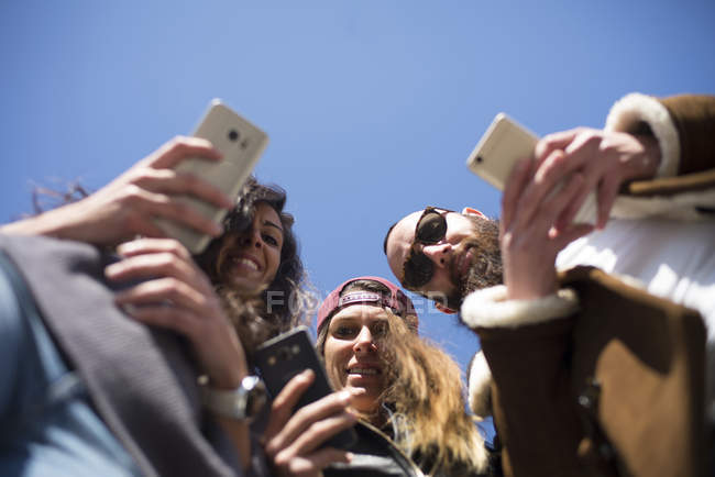 Bottom view of friends in street with smartphone — Stock Photo