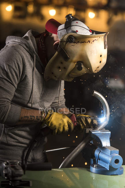 Portrait of worker in mask welding pipe at workshop — Stock Photo