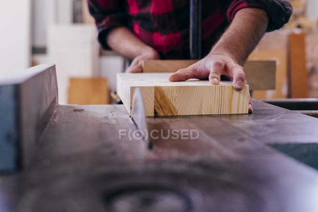 Découpe de charpentier de culture morceau de bois avec scie circulaire — Photo de stock