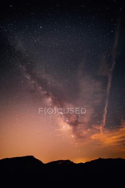 Vista panorâmica da Via Láctea no céu noturno acima silhuetas de montanha — Fotografia de Stock