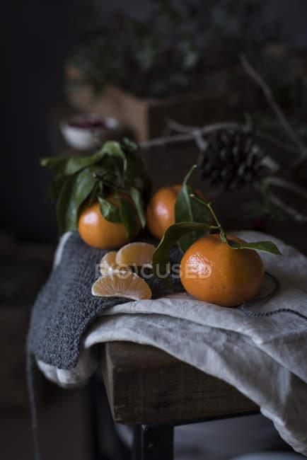 Stillleben mit kleinen Mandarinen mit Niederlassungen auf Tisch — Stockfoto