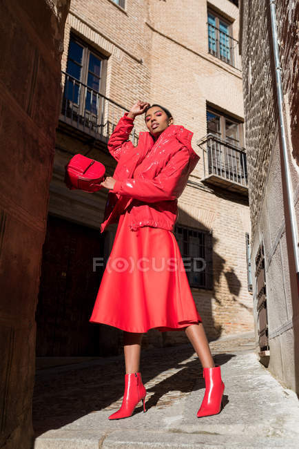 Sensual woman in red clothes posing at street — Stock Photo