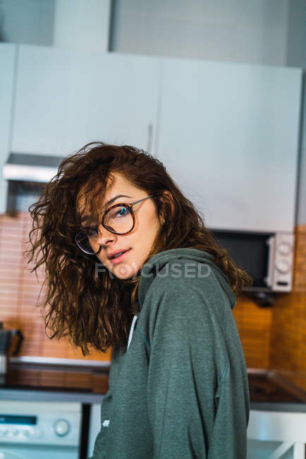 Attractive woman posing on kitchen and looking at camera — Stock Photo