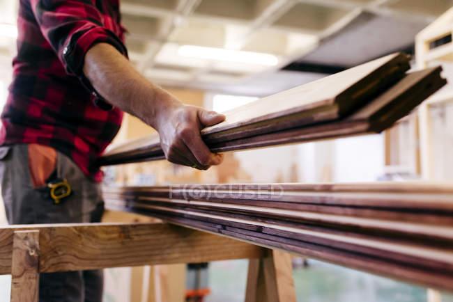 Mittelteil des Tischlers, der Holz in der Wotkshop trägt — Stockfoto