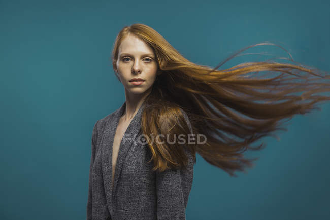 Portrait of redhead woman with waving hair on blue background — Stock Photo