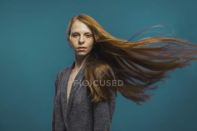 Портрет руда жінка з завивки волосся на синьому фоні — стокове фото