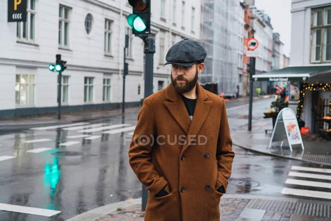 Bearded man in coat posing by traffic light at street scene — Stock Photo