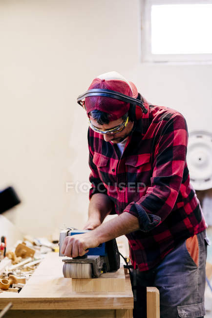 Portrait de menuisier polissage morceau de bois sur table à l'atelier — Photo de stock