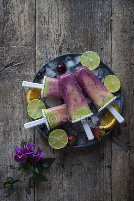 Directly above view of fruit Smoothie Popsicles in plate on wooden table — Stock Photo