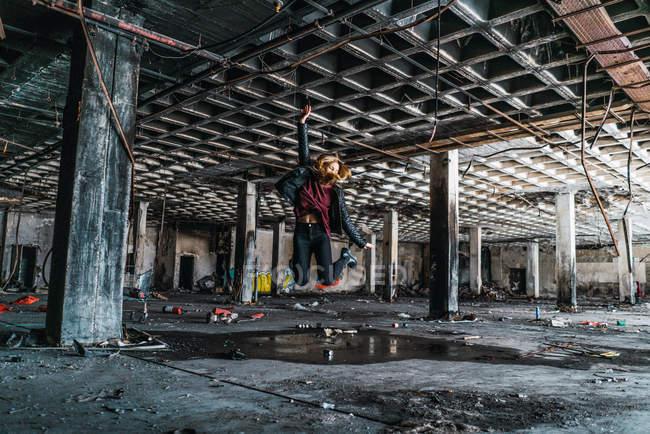 Mujer saltando en medio de la habitación abandonada envejecida . - foto de stock