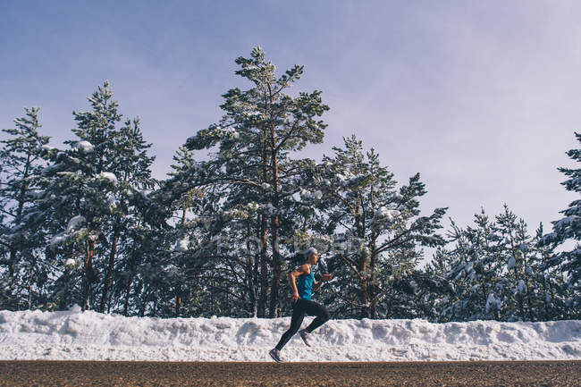Side view of fit woman running along snowy woods — Stock Photo