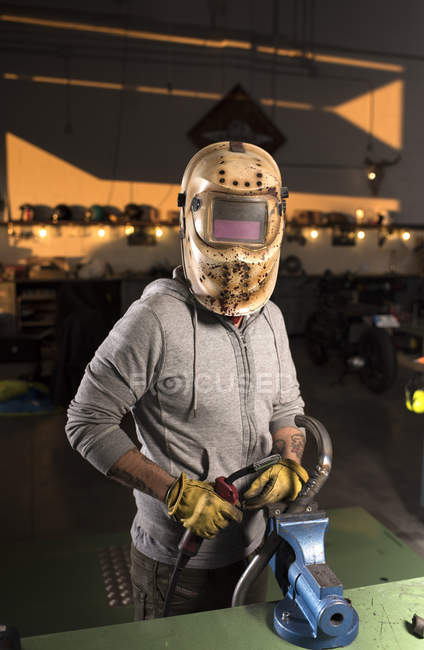 Porträt eines Mechanikers in Schweißmaske posiert an der Werkbank in der Werkstatt — Stockfoto