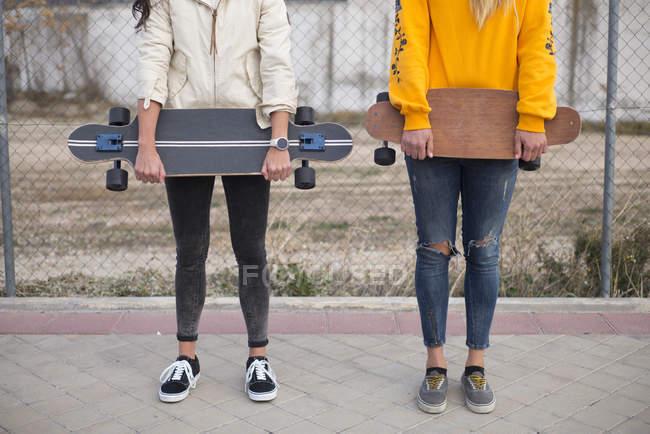 Низкий угол зрения двух девочек, позируя с longboards на улице — стоковое фото