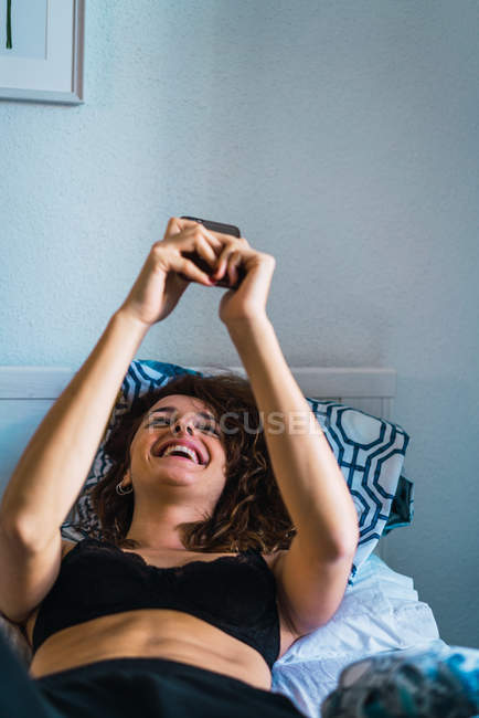 Laughing woman lying on bed and browsing smartphone — Stock Photo