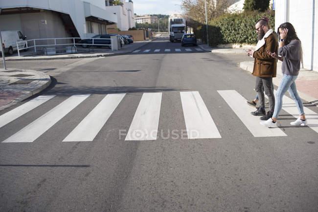 Couple of friends at zebra crossing on street scene — Stock Photo