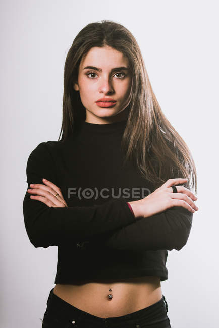 Brunette girl posing with arms crossed at studio — Stock Photo