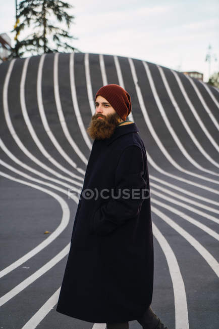 Side view of bearded man posing at asphalt hill — Stock Photo