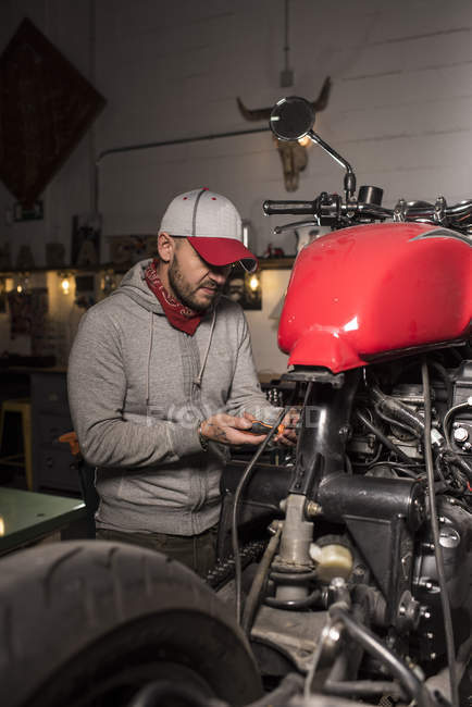 Portrait of mechanic working in custom motorbike workshop — Stock Photo